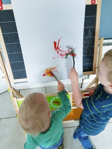 Boys painting with homemade paint brushes