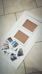 White picture frame with a selection of prints clustered in corner