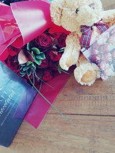 Red roses with teddy bear and box of chocolates
