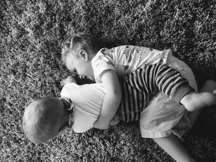 Brothers playing on a rug