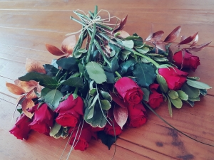 Red roses lay out on wooded table