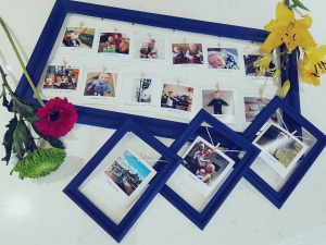 Blue Photo frames with pictures pegged. Flowers by the side