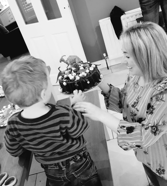 Black and white picture of mum presenting son with birthday cake.